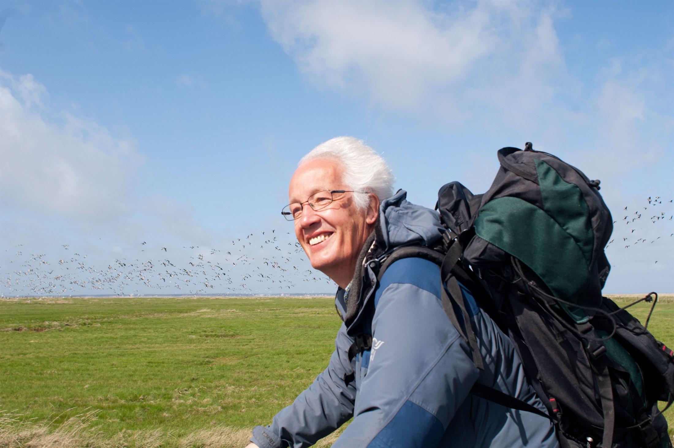 tourist-enjoying-wildlife-on-hallig-langeness-brent-geese-branta-bernicla-biosphere-reserve-halligen-germany_cf16-2200x1461px